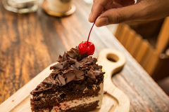 Slice of chocolate cake with cherries topping and frok on wood table. Slice of chocolate cake with cherries topping Royalty Free Stock Photography