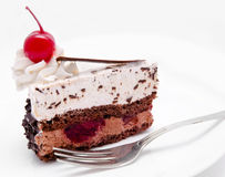Slice of chocolate cake with cherry on the top isolated Royalty Free Stock Photos
