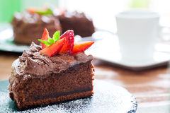 Slice of chocolate cake with coffee in background. Royalty Free Stock Photo