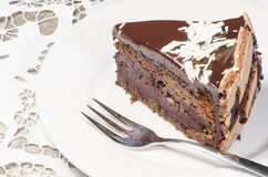 Slice of chocolate cake decorated with white chocolate flakes Stock Photography