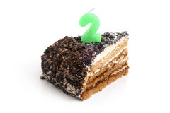 Slice of chocolate cake with number two candle Royalty Free Stock Photos
