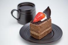 Slice of chocolate cake in saucer next to mug of coffee stock photos