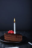 Slice of chocolate cake with a single lit candle. Stock Photography