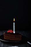 Slice of chocolate cake with a single lit candle. Royalty Free Stock Images