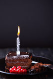 Slice of chocolate cake with a single lit candle. Royalty Free Stock Image