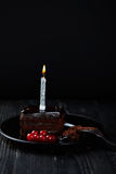 Slice of chocolate cake with a single lit candle. Stock Image