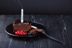Slice of chocolate cake with a single lit candle. Stock Images