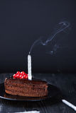 Slice of chocolate cake with a single lit candle. Stock Photo