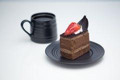 Slice of chocolate cake in saucer next to mug of coffee royalty free stock photo
