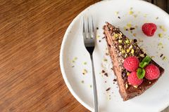 Slice of chocolate cake topped with raspberries, pistachio nut and mint leaf on white plate. Royalty Free Stock Photo