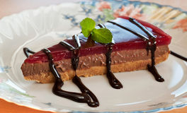A slice of chocolate cheesecake. A slice of delicious homemade chocolate cheesecake with chocolate souce royalty free stock photo