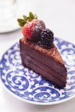 Slice of chocolate cheesecake topping with fresh strawberry and blackberry.  Royalty Free Stock Images