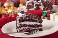 Slice of Christmas black forest gateau chocolate cake with plate and fork Royalty Free Stock Photos