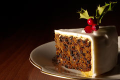 Slice Of Christmas Cake. Decorated with holly and berries Royalty Free Stock Image
