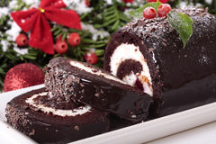 Slice of Christmas yule log cake on plate with decoration Stock Image