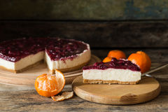 Slice of classic cheesecake with some mandarins. On wooden background Stock Photo