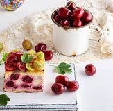 Slice of cottage cheese cake with cherry berries. On a white wooden board, behind an iron fruit mug royalty free stock photo