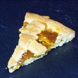 Slice of crostata cake over black stone Stock Image