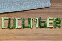 Slice cucumber on wooden background. Slice word cucumber on wooden background stock photo