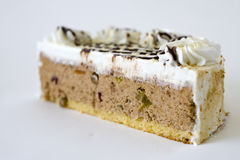 Slice of delicious cake. Close up of slice of delicious cream cake, isolated on white background Royalty Free Stock Image