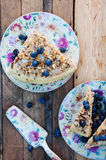 Slice of delicious  cake with fresh blueberry on wooden backgroup. Piece of blueberry cake, piece of cake on white plate with blue Stock Photo