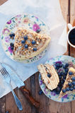 Slice of delicious  cake with fresh blueberry on wooden backgroup. Piece of blueberry cake, piece of cake on white plate with blue Stock Images