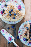Slice of delicious cake with fresh blueberry on wooden backgroup. Piece of blueberry cake, piece of cake on white plate with blueb Stock Photo