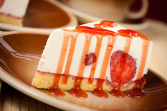 A slice of delicious cheeese cake with strawberries and syrup se Stock Images