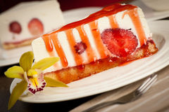 A slice of delicious cheeese cake with strawberries and syrup se Stock Photo