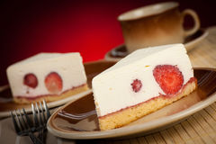 A slice of delicious cheeese cake with strawberries and syrup se Royalty Free Stock Photo