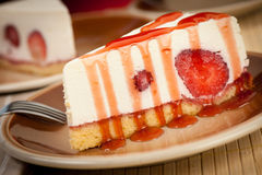 A slice of delicious cheeese cake with strawberries and syrup se Stock Photography