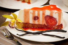 A slice of delicious cheeese cake with strawberries and syrup se Royalty Free Stock Images