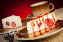 A slice of delicious cheeese cake with strawberries and syrup se Stock Image
