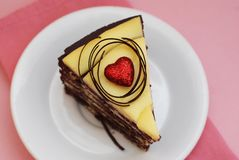 A slice of Delicious Chocolate Cake with Yellow Cream and Red Heart on a plate. Pink Background Stock Photography
