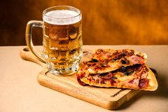 Slice of delicious homemade pizza served with light cold beer on. The wooden board on yellow brown background. Pizza time royalty free stock photography