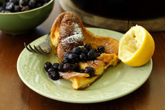 A slice of dutch baby pancake. Served on a pale green plate with blueberry compote and a lemon halve Royalty Free Stock Images