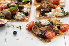 Slice of flatbread pizza on a white wooden table. Delicious a slice of flatbread pizza on a white wooden table. Top view stock image
