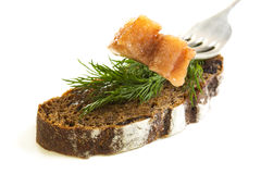 Slice on a fork herring and black bread. Stock Photo