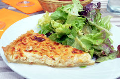 Slice of french quiche with salad served on a plate royalty free stock image