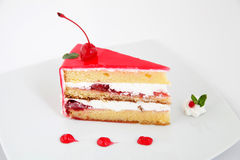 Slice of fresh cherries cake with a fresh cherry on top Stock Images