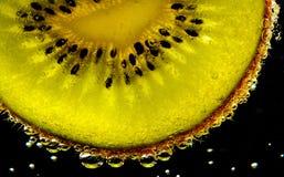 Slice of fresh fruit in water. Macro view of slice of fresh citrus fruit in water stock images