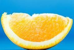 Slice of fresh juicy orange on blue background. Slice of fresh delicious juicy orange on blue background stock image