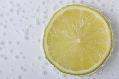 Slice of fresh lime in water with bubbles Stock Photo