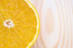 Slice of fresh orange on wooden plate Stock Images