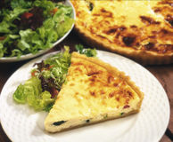 Slice of fresh quiche with salad. Close up of slice of fresh quiche on white plate with salad Royalty Free Stock Photos