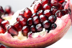 Slice of fresh ripe pomegranate fruit with seeds c. Slice of fresh ripe pomegranate fruit with seeds extreme close up royalty free stock photos