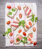 Slice of fresh rye bread with cream cheese with    red fish, cherry tomatoes and salami  parsley on a striped tablecloth on w Stock Images