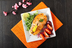 Slice of fresh salmon with tomatoes and salad. On complex background Royalty Free Stock Photo