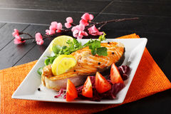Slice of fresh salmon with tomatoes and salad. On complex background Stock Photo