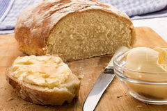Slice of freshly baked floured country bread with butter Royalty Free Stock Images